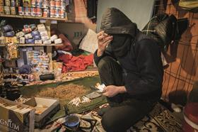 Man looks at cigarettes in Jungle shop